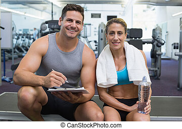 Female bodybuilder sitting with personal trainer smiling at came