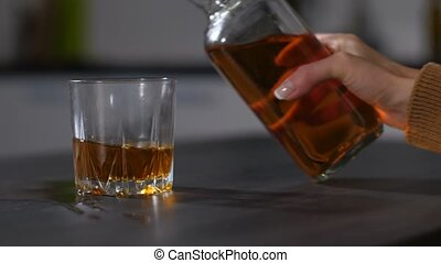 Female boozer's hand pouring alcohol into glass - Closeup of...