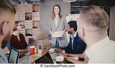Female boss gives instructions to colleagues. Happy...