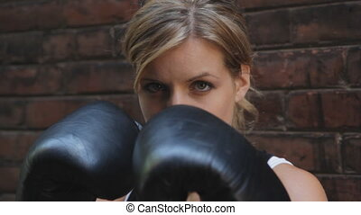 A young woman practices her boxing moves. Three shots.