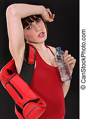 Female boxer drinking a bottle of water