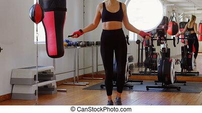 Female boxer exercising with skipping rope 4k - Female boxer...