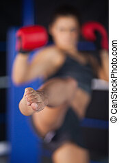 Female boxer performing an air kick