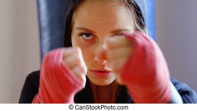 Female boxer practicing boxing in fitness studio 4k