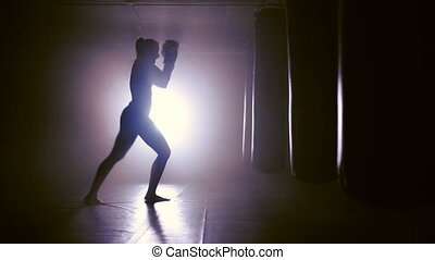 Female Boxer Punches In Boxing Gym - silhouette of a Boxer...