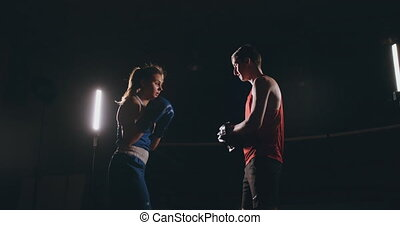 Female boxer punching a focus mitts with boxing gloves in a...