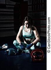 Female boxer sitting near lying boxing gloves and helmet