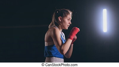 Female boxer training in dark room with backlight in slow...