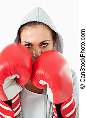 Female boxer with hoodie on in defensive stance against a...
