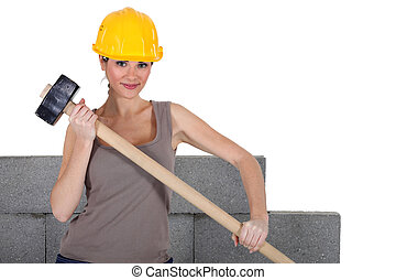 female bricklayer holding hammer against concrete wall background