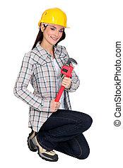 Female builder brandishing adjustable wrench