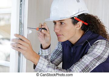 female builder fitting a window