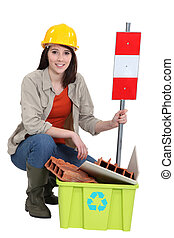 Female builder kneeling by recycle box