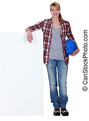 Female builder leaning against blank poster