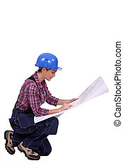 Female builder looking at architect plans