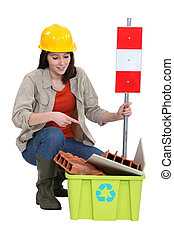 Female builder pointing to recyclable waste