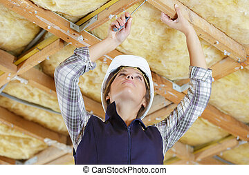 female builder working on wooden ceiling using screwdriver