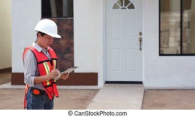 Female building inspector dressed in a white hard hat and an orange safety vest checks on her notes on the construction job site.