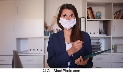 Female business assistant wearing medical face mask standing in office with clipboard, noting tasks. Concept of social distance in coronavirus pandemic. High quality FullHD footage