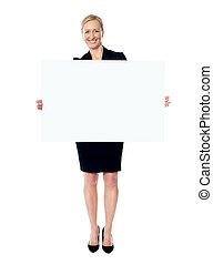 Female business promoter holding white blank banner ad