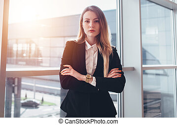Female business traveler standing against window with airport arrival corridor view