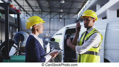 Female businesswoman and male warehouse manangers in discussion 4k
