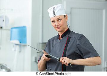 female butcher sharpening the knife