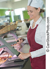 female butcher smiling while sharpening knife in butchery