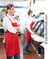 Female Butcher Standing Arms Crossed At Store