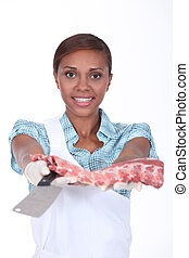 Female butcher with a rack of ribs