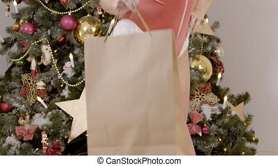 Female buttocks stand with package after shopping near Christmas tree.