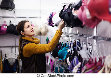 female buyer chooses bra at  store