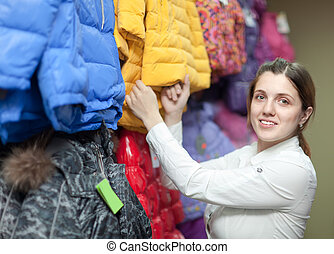 Female buyer chooses the winter jacket