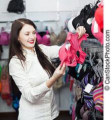 female buyer choosing bra at clothing store