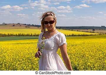 Female by a field of flowering canola and rolling hills