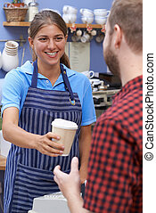 Female Cafe Worker Serving Customer With Takeaway Coffee
