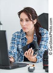 female camera technician typing on laptop