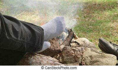 campfire - Female camper warms the feet by the campfire in...