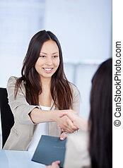Female Candidate Shaking Hands With Businesswoman