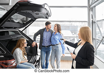 Female car dealer giving to buyers car keys.