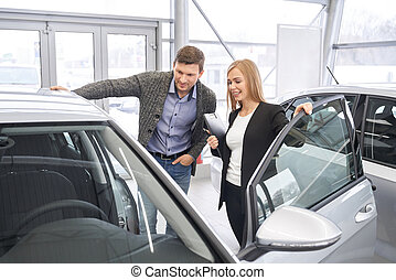 Female car dealer showing automobile to potential buyer.