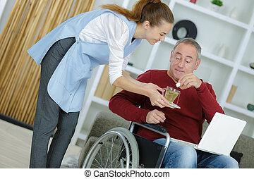 female carer giving medicine to senior man at home