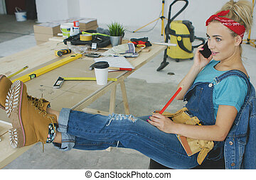 Female carpenter at workplace talking on smartphone