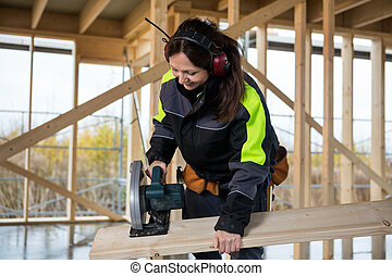 Female Carpenter Cutting Wood With Electric Saw