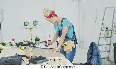 Female carpenter drawing lines on plywood sheet - Side view...