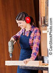 Female Carpenter Drilling Wood In Bandsaw