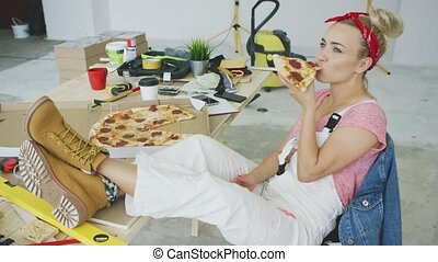 Female carpenter eating pizza at workplace - Gorgeous young...