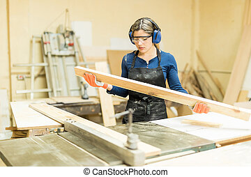 Female carpenter inspecting a piece of wood