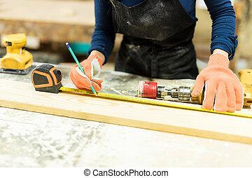 Female carpenter measuring wood