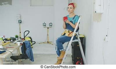 Female carpenter resting on stepladder with beverage